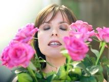 Glückliche Frau mit Rosen lizenzfreie stockfotografie