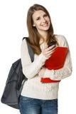 Glückliche Frau mit Rucksack und Büchern mit Handy stockfotografie