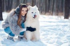 Glückliche Frau mit Samoyedhund im Winterwald Stockfotos