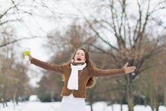 Glückliche Frau mit Schale des Heißgetränks im Winter draußen freuend Stockfoto
