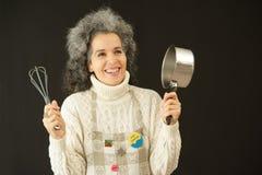 Glückliche Frau mit Schutzblech, wisk und Kasserolle Stockfotos