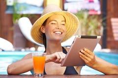 Glückliche Frau mit Tablettecomputer im Pool lizenzfreie stockfotografie