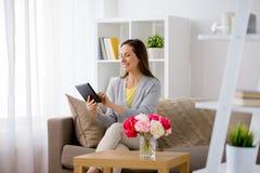 Glückliche Frau mit Tabletten-PC zu Hause Stockbilder