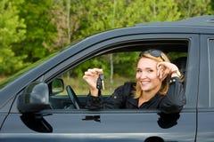 Glückliche Frau mit Tasten vom Auto Stockfoto