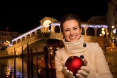 Glückliche Frau mit Weihnachtsball nahe Rialto-Brücke in Venedig Lizenzfreies Stockbild