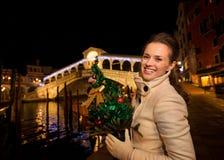 Glückliche Frau mit Weihnachtsbaum nahe Rialto-Brücke in Venedig Stockfotos