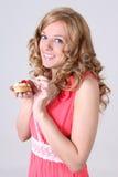 Glückliche Frau mit wenigem Kuchen in der Hand Stockbilder