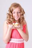 Glückliche Frau mit wenigem Kuchen in der Hand Lizenzfreie Stockbilder