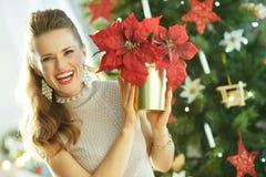 Glückliche Frau nahe dem Weihnachtsbaum, der rote Poinsettia zeigt stockfotografie