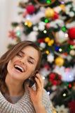 Glückliche Frau nahe dem Weihnachtsbaum, der Telefonaufruf bildet Stockfotos