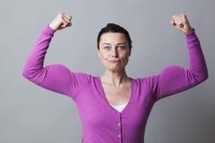 Glückliche Frau 40s, die ihre Muskeln für Metapher der weiblichen Energie anhebt Lizenzfreies Stockfoto