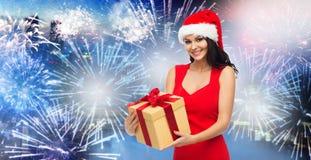 Glückliche Frau in Sankt-Hut mit Geschenk über Feuerwerk Stockbild