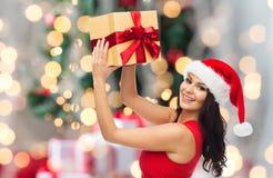 Glückliche Frau in Sankt-Hut mit Geschenk über Lichtern Stockfotos