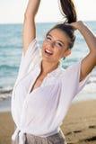 Glückliche Frau am Strand, der ihr Haar anhebt Stockfotografie