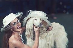 Glückliche Frau und Hund in den Retro- Hüten Sinnliches Frauenlächeln zum lustigen Haustier Modemädchen und Haustier Freundschaft stockbilder