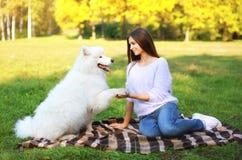 Glückliche Frau und Hund, die im Park stillsteht Lizenzfreies Stockbild