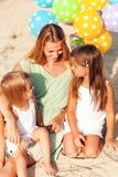 Glückliche Frau und ihre kleinen Töchter am Strand mit Ballons Stockfotografie