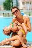 Glückliche Frau und ihre Tochter nahe Pool Lizenzfreie Stockfotografie