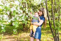 Glückliche Frau und Kind im blühenden Frühling arbeiten im Garten Muttertagesfeiertagskonzept stockfotografie