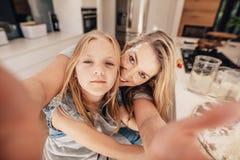 Glückliche Frau und Mädchen, die ein selfie in der Küche nimmt Lizenzfreies Stockbild