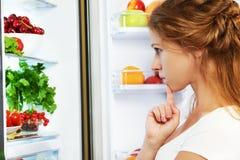 Glückliche Frau und offener Kühlschrank mit Früchten, Gemüse und ihm stockbild