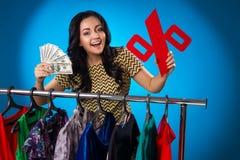 Glückliche Frau unter dem Kleidungs-Gestell mit Kleidern Stockfotografie
