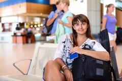 Glückliche Frau von mittlerem Alter in einem Flughafenaufenthaltsraum lizenzfreie stockfotos