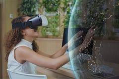 Glückliche Frau in VR-Kopfhörer, der einen Planeten 3D berührt Stockfotos