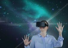 Glückliche Frau in VR-Kopfhörer, der oben gegen grünen und purpurroten Raumhintergrund schaut Stockfoto