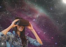 Glückliche Frau in VR-Kopfhörer, der zu einem rosa Galaxiehintergrund schaut Lizenzfreies Stockbild