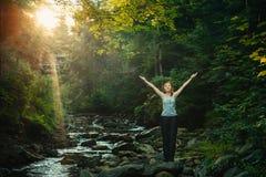 Glückliche Frau, welche die Natur im Wald genießt Stockbild