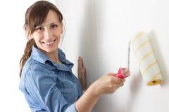 Glückliche Frau, welche die Wand malt Stockfotografie