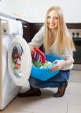 Glückliche Frau, welche die Waschmaschine lädt Stockfoto