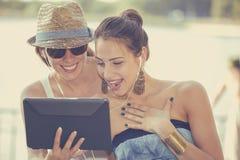 Glückliche Frauen überraschten das Teilen von Social Media-Nachrichten auf Auflagencomputer stockfoto