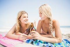 Glückliche Frauen, die auf dem Strand mit Bierflasche liegen Stockfoto