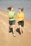 Glückliche Frauen, die auf Strand laufen Stockbilder