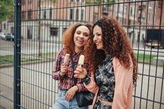 Glückliche Frauen, die draußen eine Eiscreme essen Stockfotos