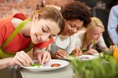 Glückliche Frauen, die Gerichte kochen und verzieren lizenzfreie stockbilder