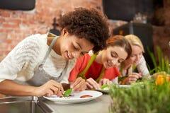 Glückliche Frauen, die Gerichte kochen und verzieren stockfoto