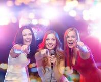 Glückliche Frauen, die Karaoke und das Tanzen singen lizenzfreie stockfotografie