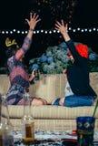Glückliche Frauen, die Konfettis zur Luft in der Partei werfen Stockfotografie