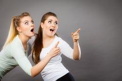 Glückliche Frauen, die oben mit einem Finger zeigen Stockfotos