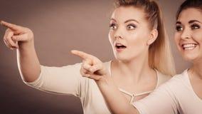 Glückliche Frauen, die oben mit einem Finger zeigen Stockfoto