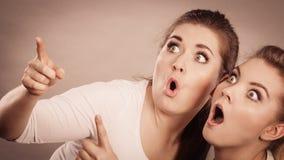 Glückliche Frauen, die oben mit einem Finger zeigen Lizenzfreie Stockfotos