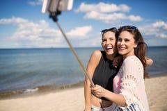 Glückliche Frauen, die selfie auf Strand nehmen Stockbilder