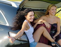 Glückliche Frauen, die von der Rückseite des Autos trampen Stockfotos