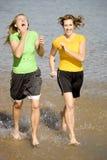 Glückliche Frauen, die in Wasser laufen Stockfotografie