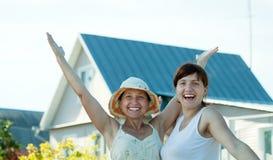 Glückliche Frauen gegen neues Haus Stockfotos