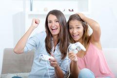 Glückliche Frauen mit dem Steuerknüppel, der Videospiele spielt lizenzfreie stockfotos