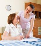 Glückliche Frauen mit Finanzdokumenten bei Tisch Lizenzfreie Stockbilder